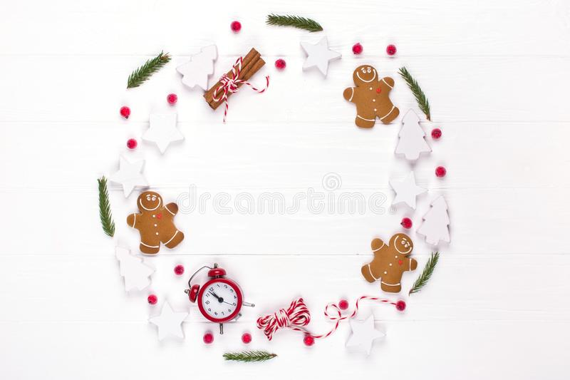 Christmas composition. Round frame made of decorations, fir tree branches, gingerbread man cookies on white background. Winter ho royalty free stock images