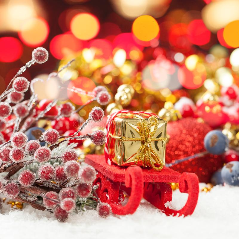 Christmas composition with Santa sleigh, gold gift and colorful Xmas decoration against abstract bokeh light background stock image