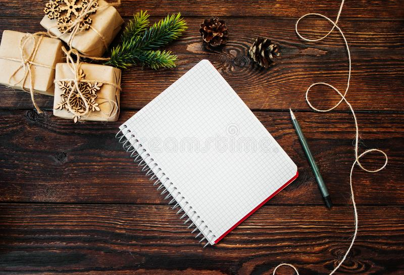 Christmas Composition set of gift kraft boxes and wooden toys, corn and note with pen on wooden background stock images