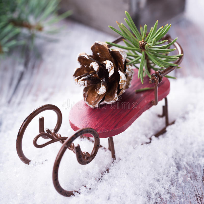 Christmas composition with sleigh, pinecone and decoration. On snow. Christmas greeting card stock photo