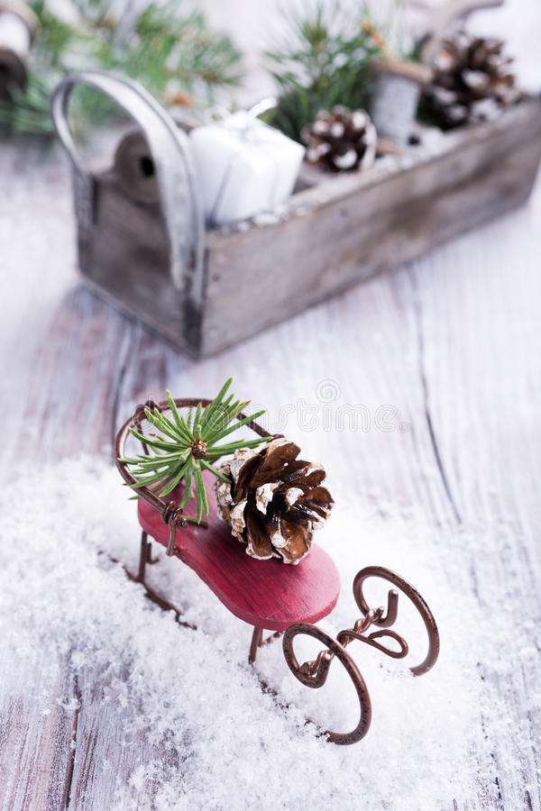Christmas composition with sleigh, pinecone and decoration. On snow. Christmas greeting card stock image