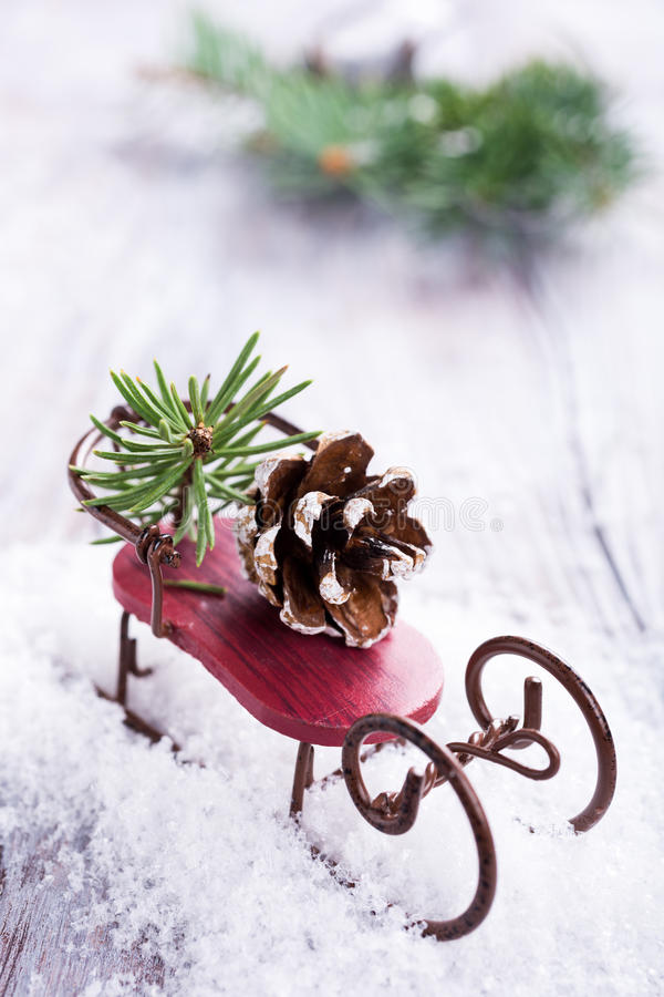Christmas composition with sleigh, pinecone and decoration. On snow. Christmas greeting card royalty free stock photo