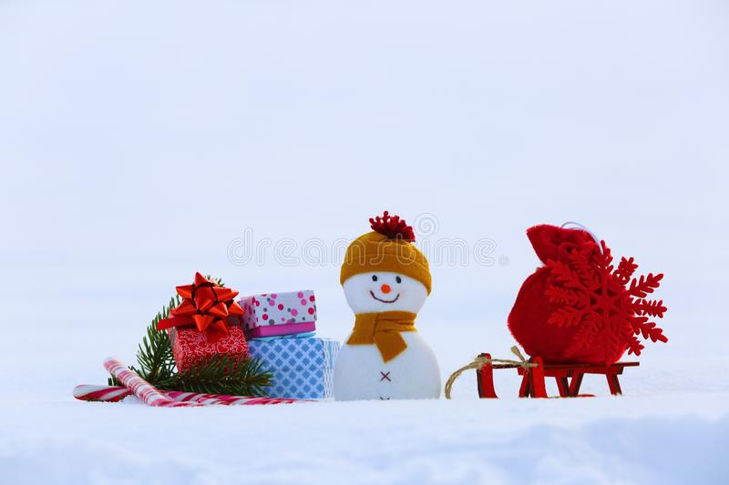 Christmas composition with snowy background. Snowman with red bag with the snowflake on the sledge. Colorful gift box. stock photo