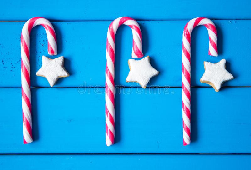 Christmas composition with star-shaped gingerbread cookies and candies on blue background royalty free stock photos