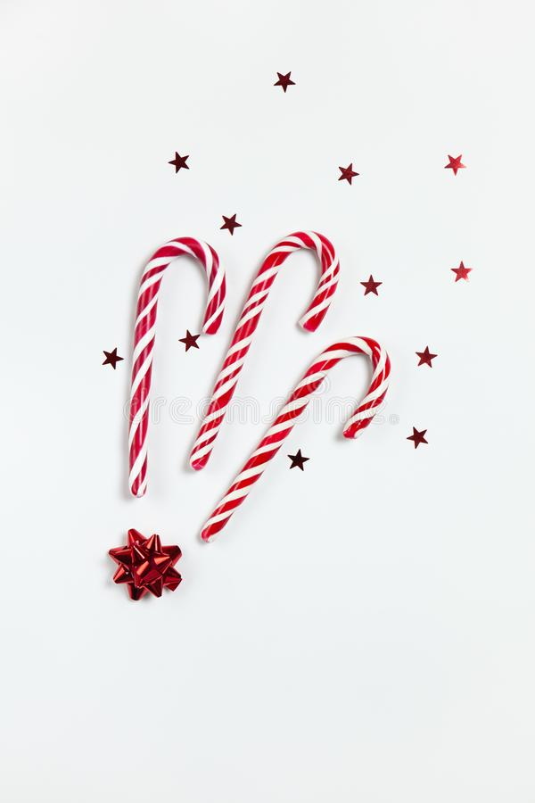 Christmas composition three caramel candy canes, confetti stars and red bow on white background. Festive minimal style flat lay. royalty free stock image