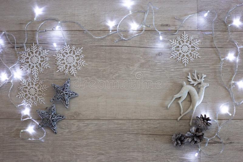 Christmas composition: a toy deer, snowflakes, silver stars and garland. Lights on a white wooden background. Top view, copy space royalty free stock image
