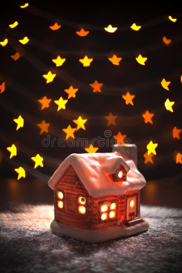 Christmas composition. Toy house on a black background blurry defocused lights in form star. Christmas, winter, new stock photos