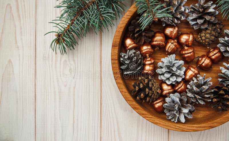 Christmas composition.Tree banch,white cones and golden acorns in the wooden plate. stock images