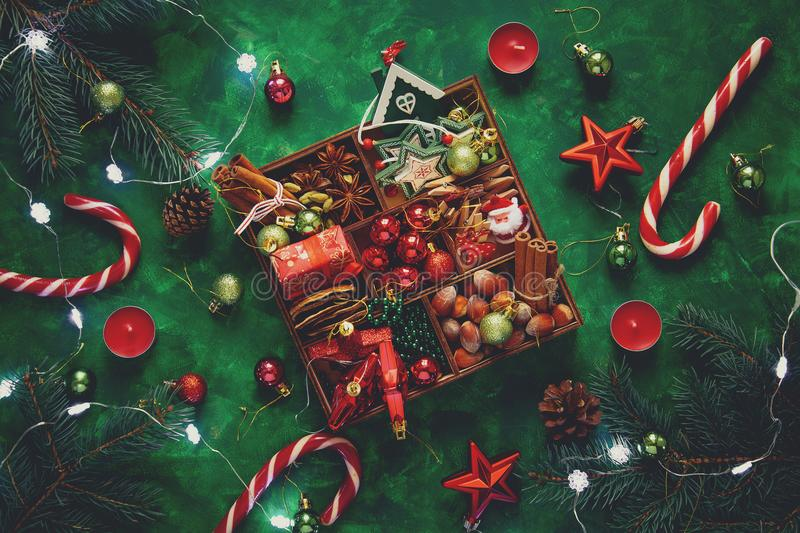 Christmas composition. Christmas tree and box with spices and toys on green wooden background stock photos