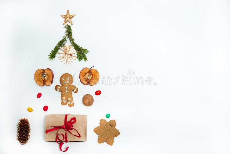 The tree is made of gingerbread, gift boxes, slices of dried apples, cones, walnuts, candy and straw toys on a white background. C royalty free stock images