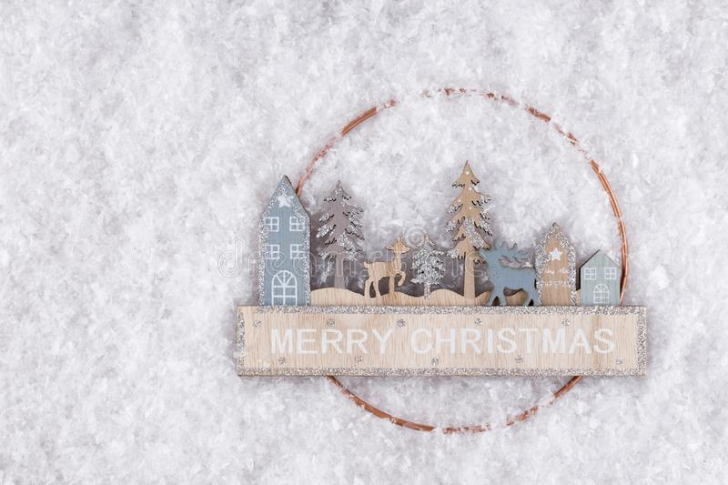 Christmas trees, houses, deer made of wood on a background of snow and Merry Christmas inscription. royalty free stock photos