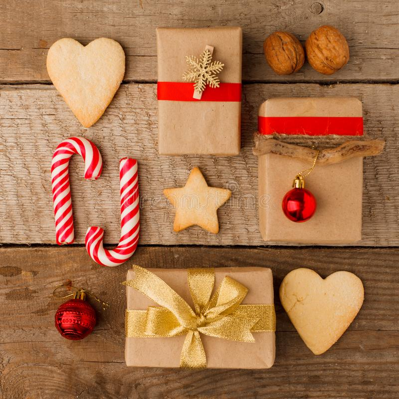 Christmas composition of various gift boxes wrapped in craft paper and decorated with satin red gold ribbons and holiday sweetness stock photo