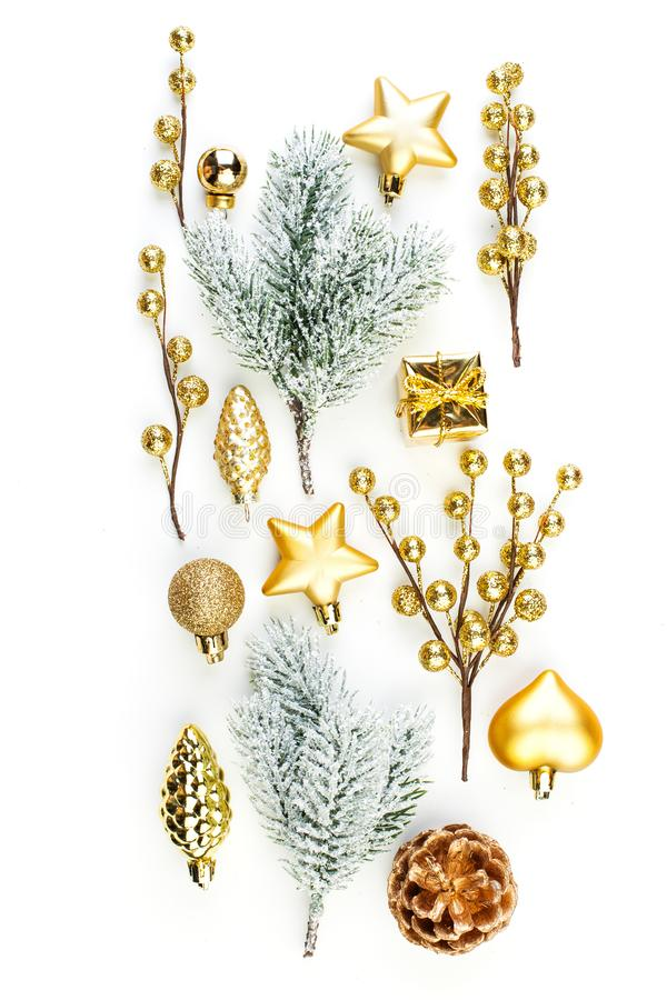Christmas composition on white background. Golden decorations and winter fir twig isolated. Christmas or New Year concept. Flat lay, top view royalty free stock photo