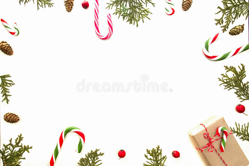 Christmas composition on white background. Xmas gift, green thuja twigs, pine cones and red wild rose fruits. Top view. Flat lay. Winter holidays concept stock photography