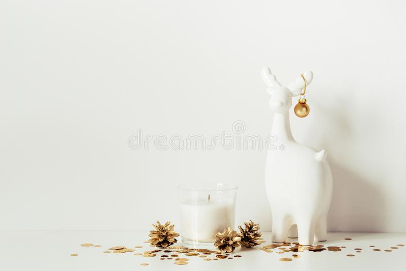 Christmas composition with White deer, candle and gold sparkles. Front view. Copy space for artwork.  stock image