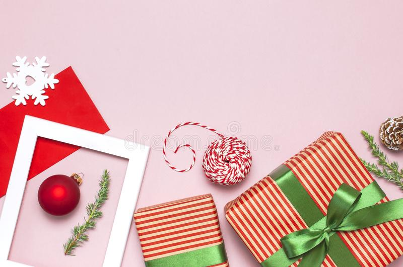 Christmas composition. White photo frame, red envelope, fir branches, cones, ball, twine, gift, wooden toys on pink background. Flat lay top view. Christmas stock images
