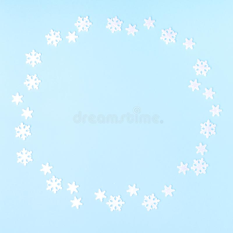 Christmas composition. Wreath made of snowflakes on pastel blue background. Flat lay, top view, copy space royalty free stock image