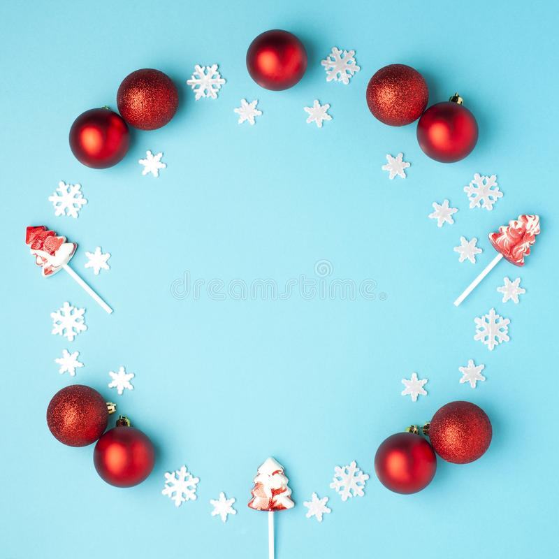 Christmas composition. Wreath made of snowflakes, red balls and lollipops on pastel blue background. Christmas, winter, new year royalty free stock image