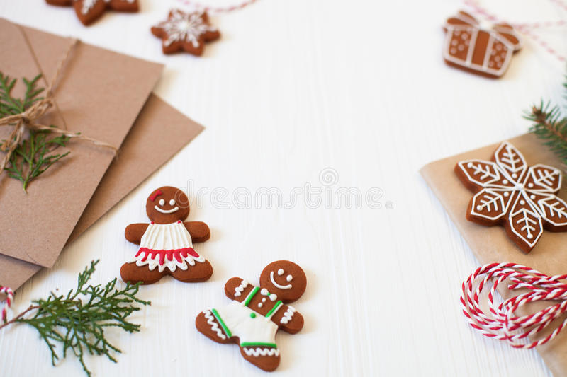 Christmas composition. Xmas cookies, Gingerbread man, ribbon, ca. Rd, festive decoration, fir branches on white wooden background. Flat lay, top view, with copy stock photos