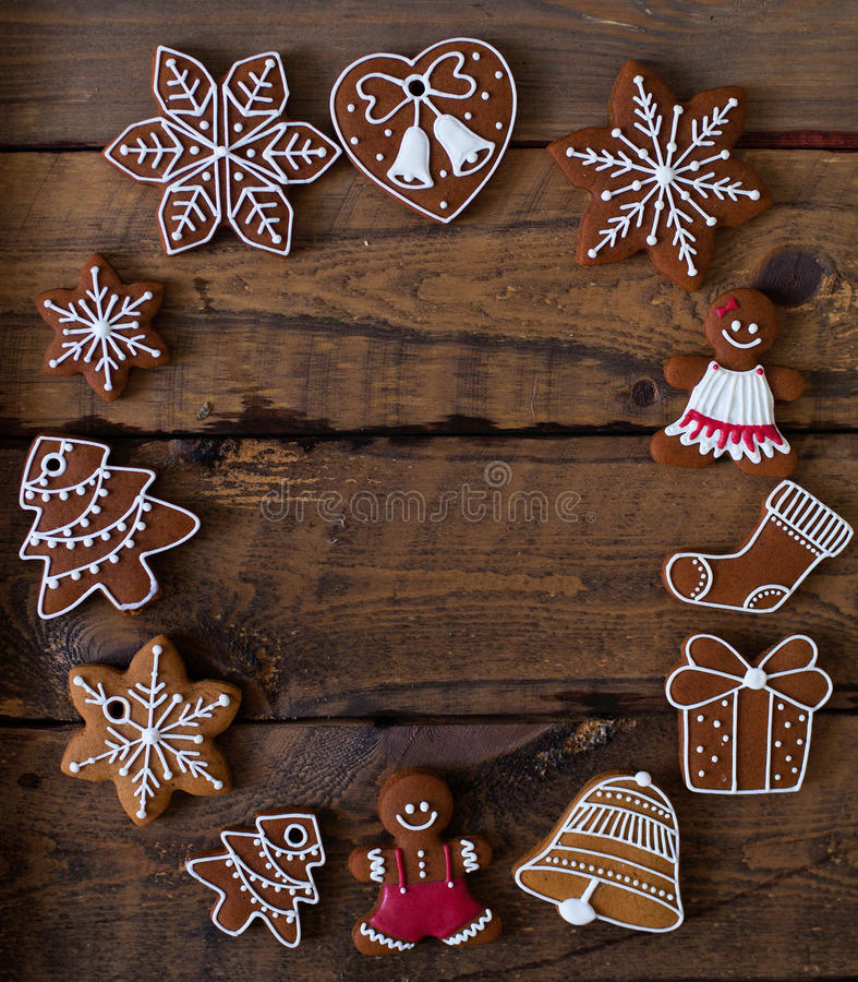 Christmas composition. Xmas cookies, Gingerbread man, tangerines. Cinnamon, festive decoration, fir branches on dark old wooden background. Copy space stock photo