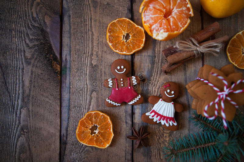 Christmas composition. Xmas cookies, Gingerbread man, tangerines. Cinnamon, festive decoration, fir branches on dark old wooden background. Flat lay, top view royalty free stock photography