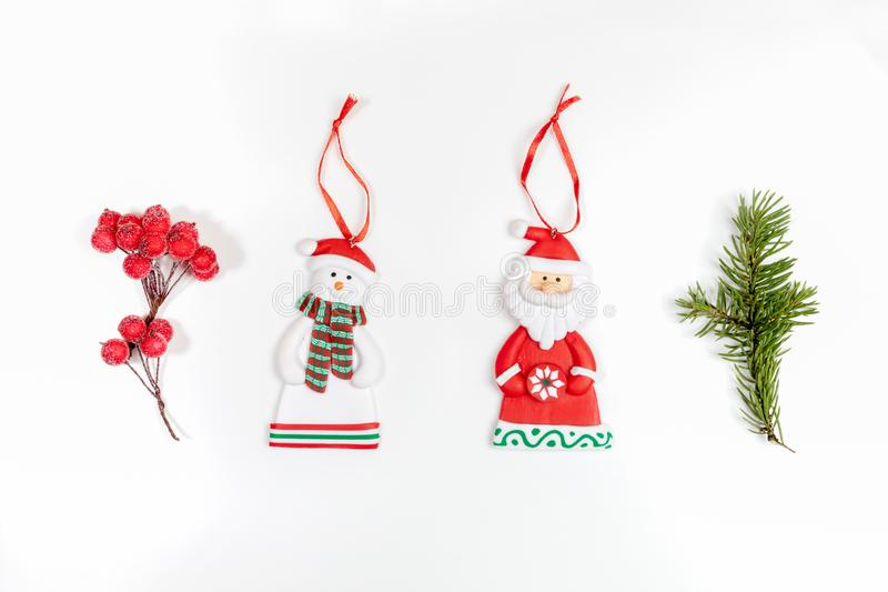Christmas composition with xmas tree branch, red berries and xmas toys santa claus and snowman on white background stock photography