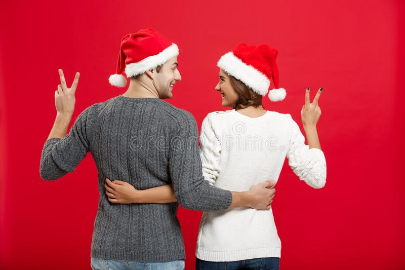 Christmas Concept - back view of portrait lovely young couple showing two finger gesture stock photos