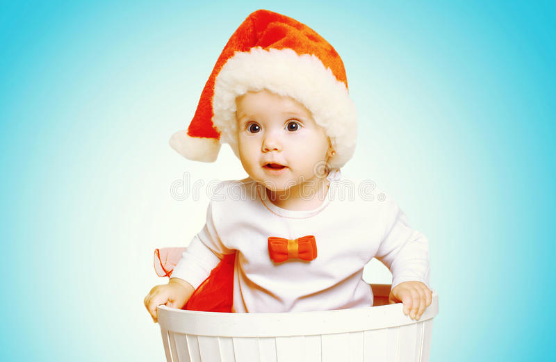 Christmas concept - beautiful baby in santa red hat gets out of the container stock image
