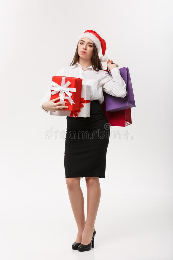Christmas Concept - beautiful business woman holding shopping bags and present with exhausted feeling. royalty free stock photography