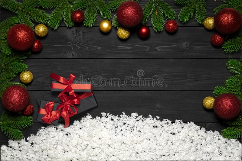 Christmas concept decoration with snow, xmas gift boxes with red ribbon, new year balls, fir branches black wooden background royalty free stock photo