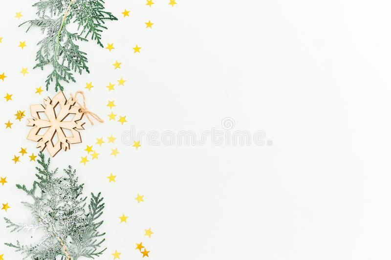 Christmas concept. Fir branches and wooden decoration with golden confetti on white background. Flat lay, top view royalty free stock images