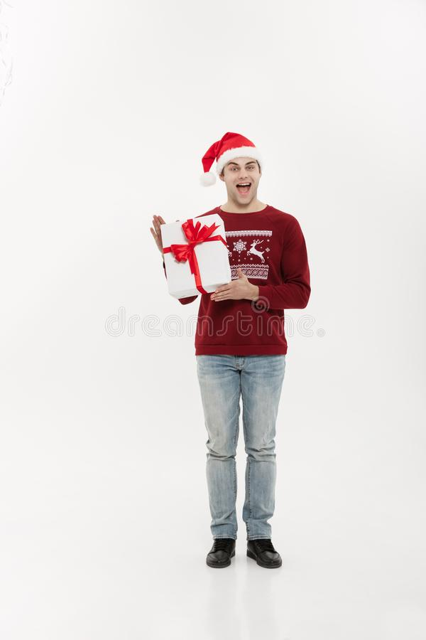 Christmas Concept - Full-length handsome young man in sweater wi stock photo