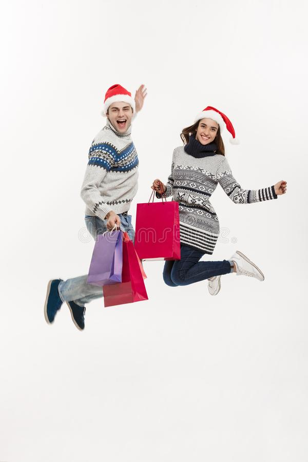 Christmas Concept - Full length Young attractive couple holding shopping bags and jumping isolated on white grey stock photography