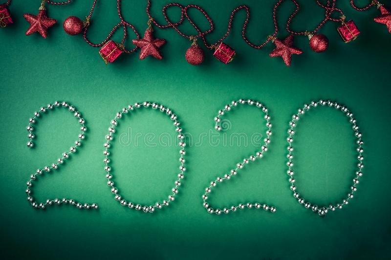 Christmas concept with garland with stars and gift boxes. 2020 made from white beads on the green background. Top view and copy royalty free stock photos