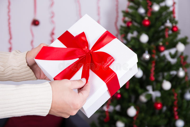 Christmas concept - gift box in male hand. Over Christmas interior royalty free stock photography