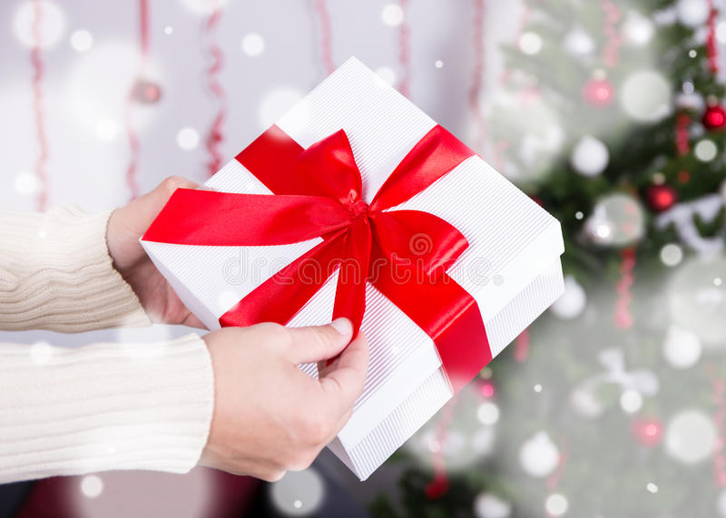 Christmas concept - gift box in male hands. Over decorated Christmas interior stock photo