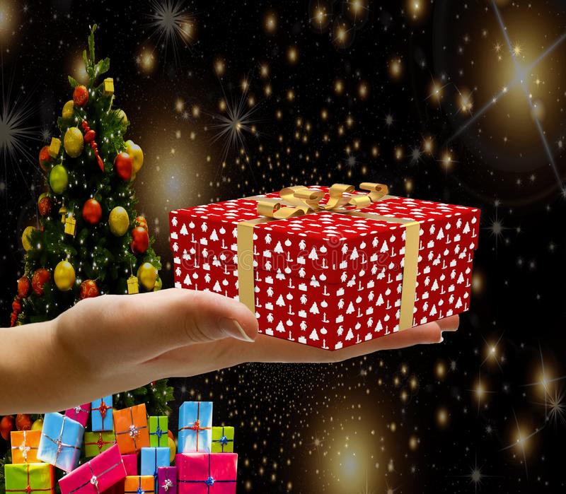 Christmas concept a hand holding a decorated wrapped christmas present box isolated on a christmas background with stars a tree an stock photos