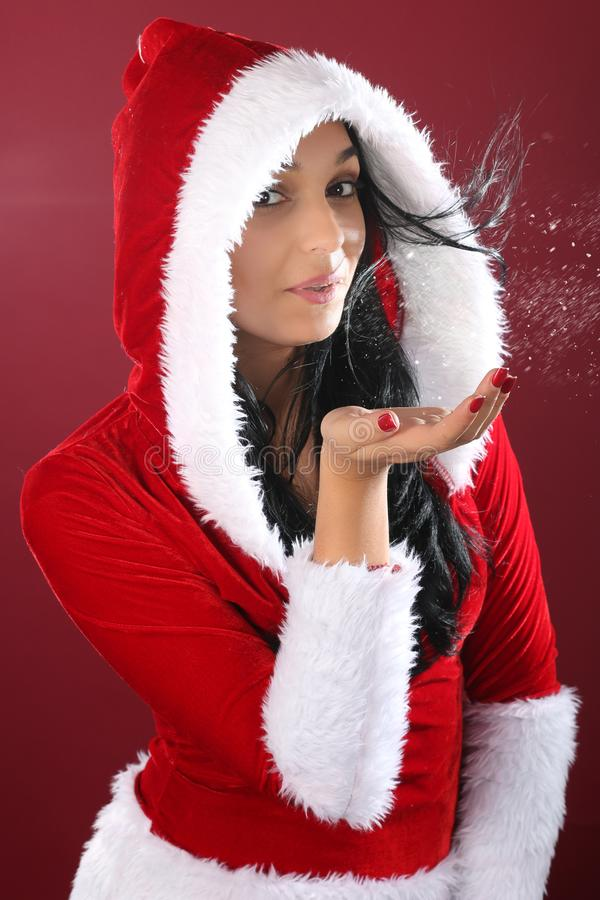 Christmas concept - happy woman in Santa clothes blowing snow on palms royalty free stock photography