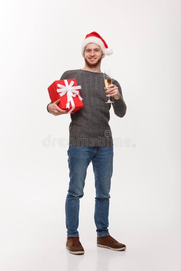 Christmas Concept - Happy young man with beard holding present and champagne celebrating for Christmas isolated on white stock photography
