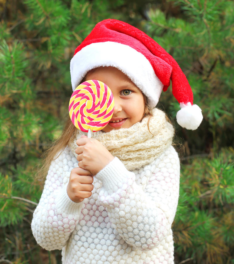 Christmas concept - little child in santa red hat with sweet lollipop stock images