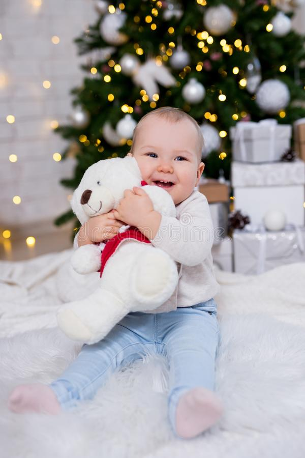 Christmas concept - little girl with toy near decorated christmas tree. Christmas concept - portrait of  little girl with toy near decorated christmas tree stock image