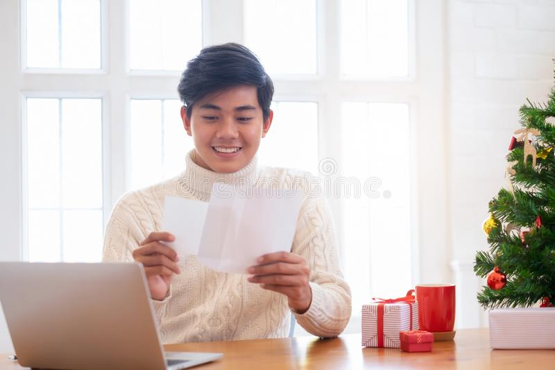 Christmas concept. Man opening christmas card. Christmas concept. Man wearing white sweater opening and sending christmas card royalty free stock images