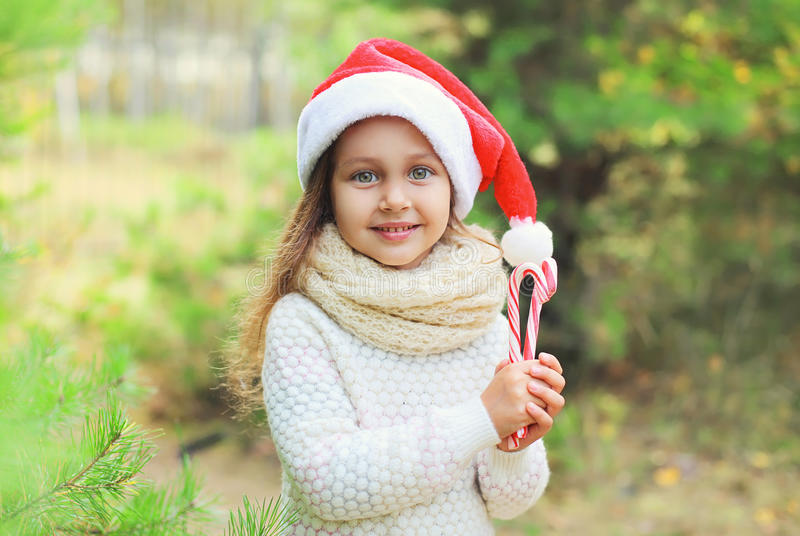 Christmas concept - portrait little girl child in santa red hat with sweet lollipop cane. Christmas and people concept - portrait little girl child in santa red stock images