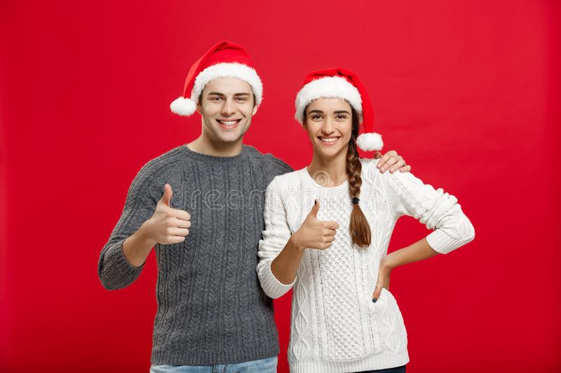 Christmas Concept - portrait lovely young couple showing thump up gesture with finger to camera stock photography