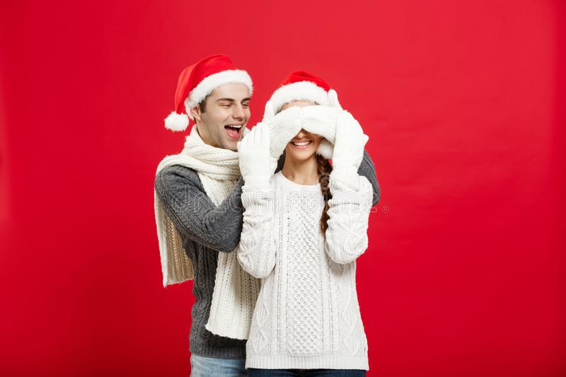 Christmas concept - Portrait of a romantic young boyfriend surprising girlfriend over red studio background stock image