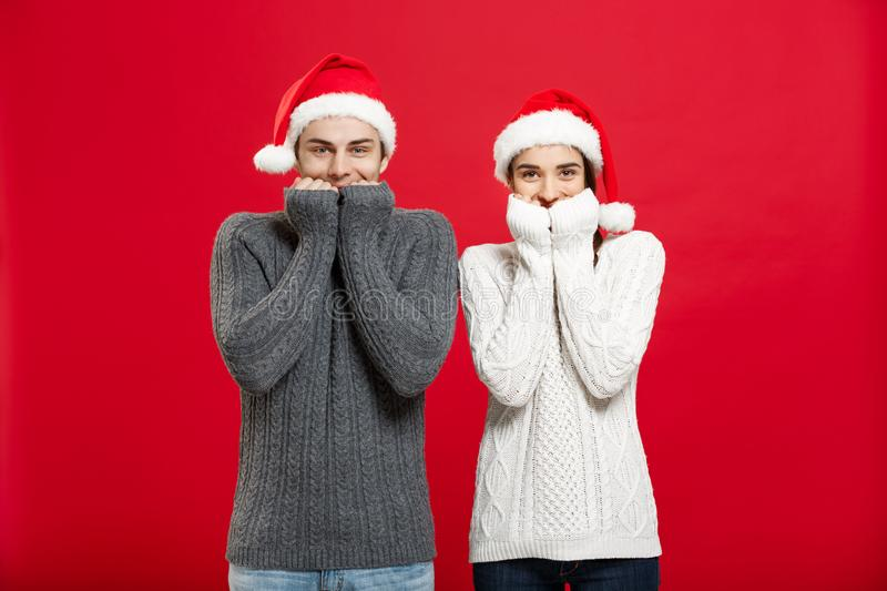 Christmas Concept - Portrait of smiling mouth tapping couple looking in camera with opened eyes over red studio stock photo