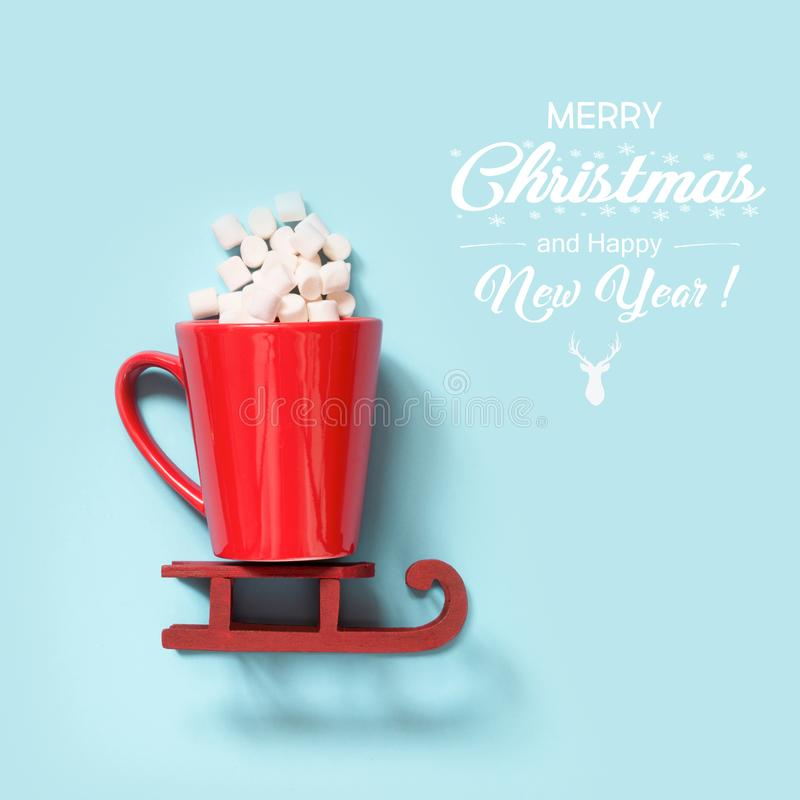 Christmas concept. Red cup with marshmallow on red sleidge over blue background. Square. Holiday cheers. royalty free stock image