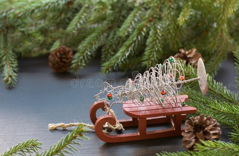Christmas concept with red sleigh, pine cones and fir tree branch on black background.Copy space. stock images