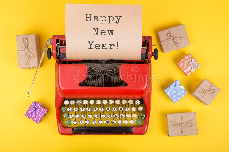 Christmas concept red typewriter with the text & x22;Happy New Year!& x22;, gift boxes and wrapping paper on yellow background. Christmas concept - red royalty free stock photo