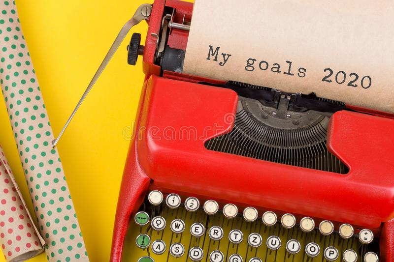 """Christmas concept - red typewriter with the text """"My goals 2020"""" and wrapping papaer on yellow background royalty free stock photography"""